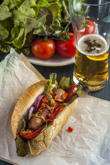 Hotdog with sausage and vegetables and glass of beer