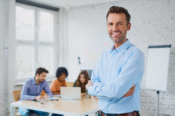Happy businessman standing in the office with coworkers in the b
