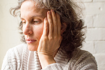 Middle aged woman in grey cardigan with hand on head, looking pensive (selective focus)