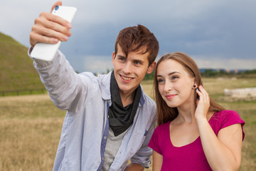 Two friends with mobile phone taking selfies.  Summer time.