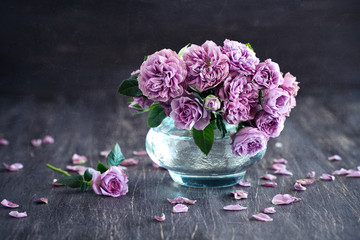 Beautiful fresh purple roses in a vase on a dark brown wooden background .