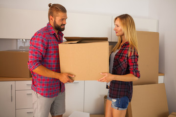 Young couple just move to their new apartment. They are unpackin