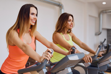Two happy woman training indoor cycling at gym