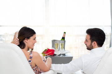 Romantic couple in hotel room celebrating with champagne.
