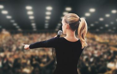 Donna motivatore indica su palco
