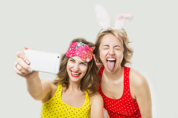 Mobile phone, internet, selfie. Two woman funny friends having fun calling to friends and fooling. Pijamas party cool active mood festive atmosphere.