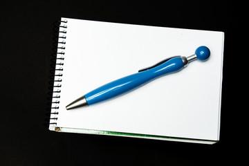 blue pen on notebook on black background