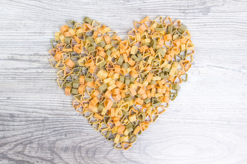 Pasta lined heart on wooden background, view from the top