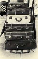 Stack of old battered suitcases with vintage style filter applied to image