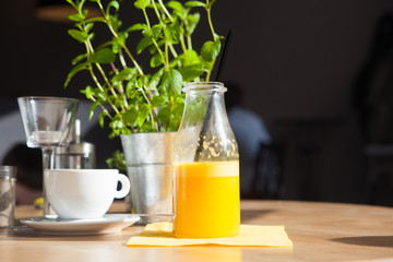 Bottle of Freshly squeezed orange juice sitting on a rustic wooden table.