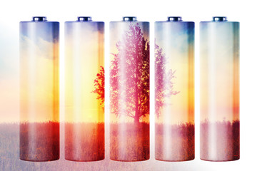 Double exposure of batteries and landscape with tree, environmen