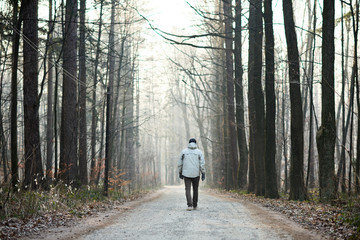 Man walking away down road between trees in winter forest