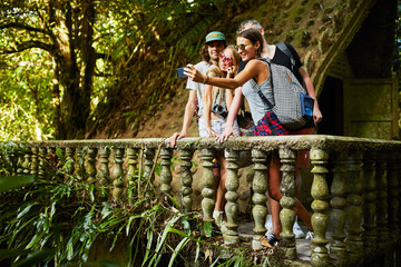 group of tourists taking selfie on ancient jungle ruins in thailand tropical rain forest