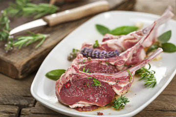 Rohes Lammfleisch mit Stiel mariniert auf weißem Teller