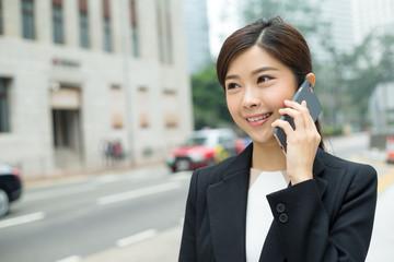 Businesswoman talk to cellphone in Hong Kong city