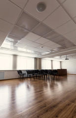 Projector hang on ceiling of empty sunlit meeting room