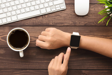 hand using smartwatch on desk top view