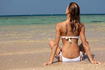 femme en maillot assise de dos à la plage