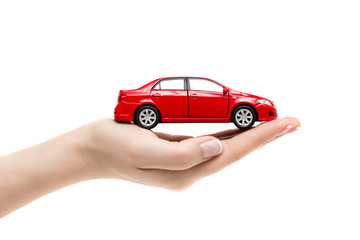 Toy car on female hand on white background.