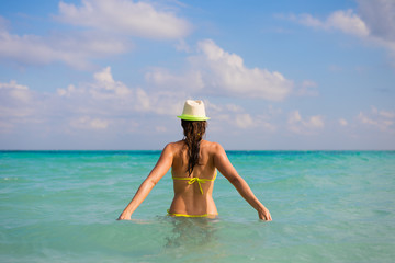Back view of young woman on summer caribbean travel and vacation.
