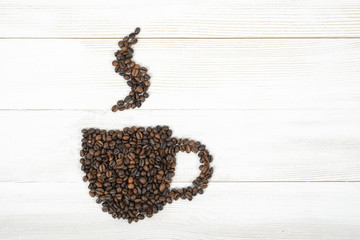 Cup of fragrant hot coffee made by beans on wooden background