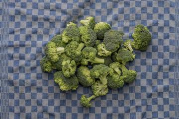 Fresh organic broccoli on a blue checkered kitchen towel