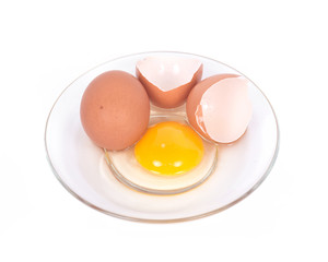Cracked brown eggs on plate separated on white background
