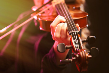 Musician play violin on dark background, close up