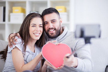 Happy young beautiful couple taking photo with smart phone on selfie stick. Young couple having fun in the living room