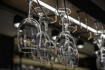 Wine glasses hanging over a bar rack.
