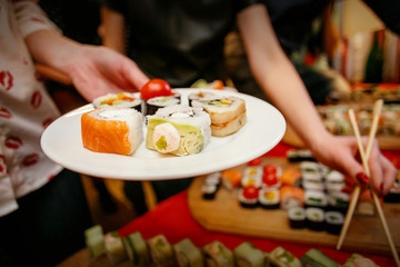 Photo sur Aluminium Assortiment Sushi lunch, hands with chopsticks