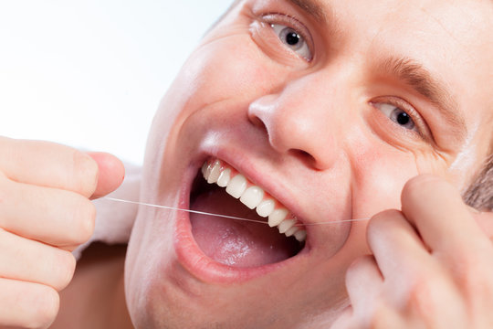 Young man cleaning her white teeth with dental floss