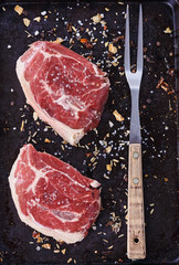 Red meat and fork over rustic metal background