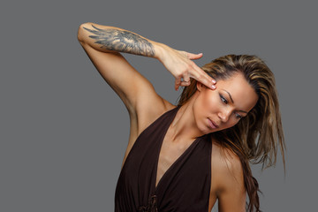 A woman in a brown dress with tattoo on her hand.