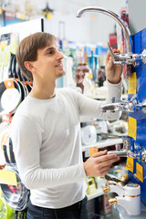 Young male choosing faucets in hypermarket.