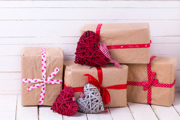 Festive gift boxes and  grey and red decorative hearts  on white