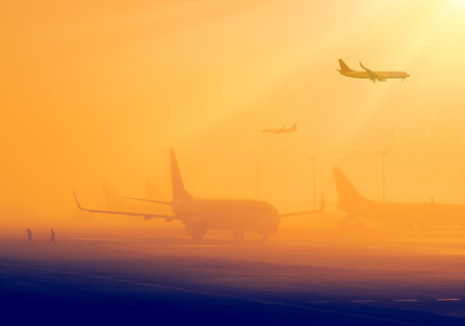 Airport in a foggy weather - silhouettes of airplanes early in the morning. Aircrafts in a fog, international airport at sunrise. Air travel - passenger and commercial transportation.
