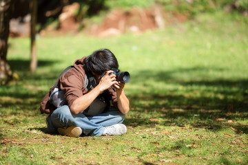 Young man is taking a photo outside in the garden.