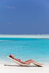 femme qui bronze sur une plage de sable blanc paradisiaque