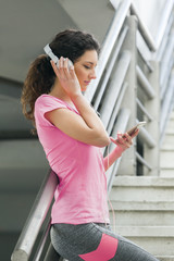 Fitness girl listening to music between workouts