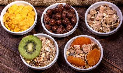 assortment of different breakfast with oatmeal, cereal, dried fruit, kiwi in plates on a wooden table