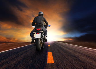 man riding motorcycle on highway against beautiful  sun set sky