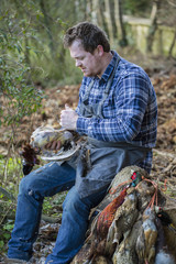 A man sitting on a tree stump plucking feathers from a game bird carcass.