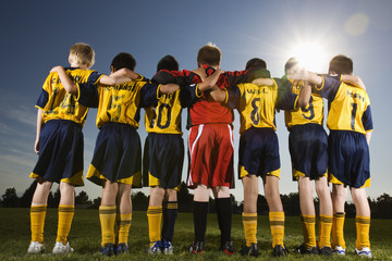 A team of soccer players standing in a row, arms around each other.