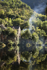 Houses on a steep hillside, reflected on the water of a river. Woodland, and a thin stream of rising wood smoke.