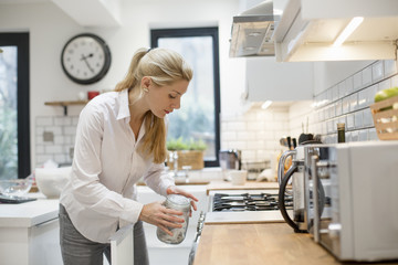 A woman in a modern kitchen holding a jar with a lid.