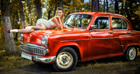 Pin-up girl in white dress on the hood of red retro car on a background of green forest