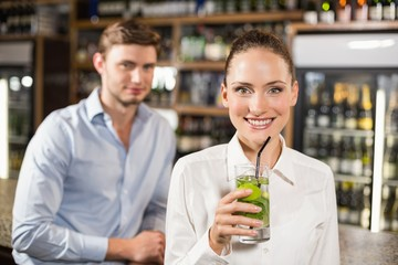 Woman drinking beverage in front of man