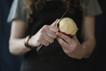 A woman in a blue apron peeling an apple with a knife.