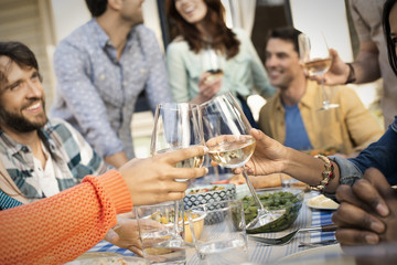 Friends around a table, men and women laughing and clinking wine glasses in a toast.